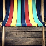 Recline: A deck-chair, ready for bottom of a relaxing holiday-maker on Bournemouth Pier.